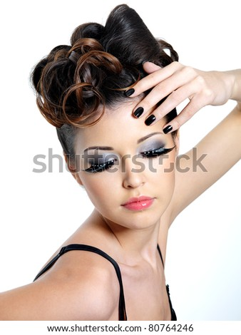 Glamour woman with  fashion eye make-up   and black nails near the face - stock photo