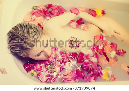 Glamour woman with silk skin having bath in rose petals