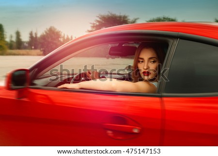 glamour young woman with red lips driving a car and looking away