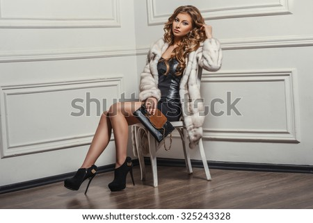 Glamourous portrait of the young beautiful woman in leather boots and stylish handbag. Trend fashion look. Beauty Fashion Model Girl in White Mink Fur Coat. Beautiful Luxury Winter Woman - stock photo
