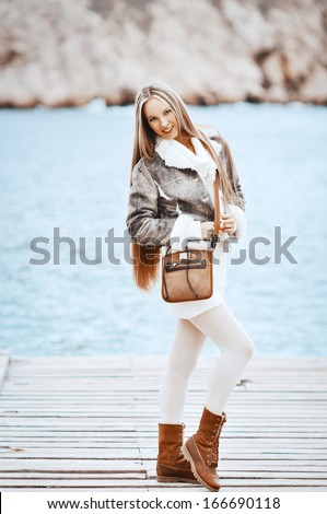 glamourous portrait of the young beautiful woman in leather boots on the bank of a beach - stock photo