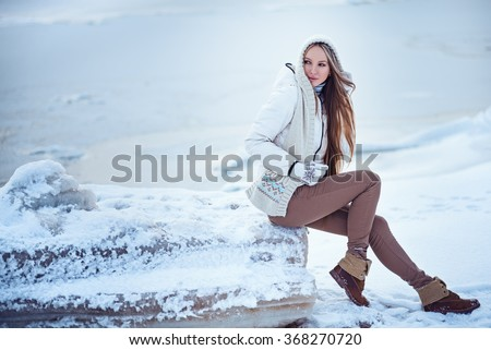 glamourous portrait of the young beautiful woman in leather boots on the bank of a sea on an ice floe - stock photo