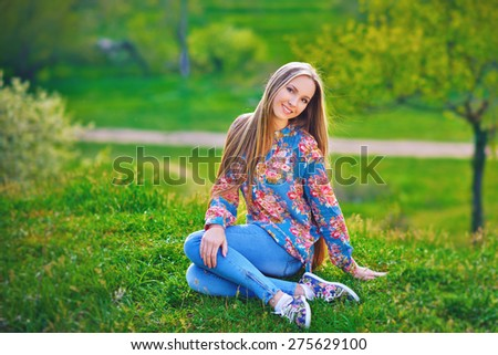 Glamourous portrait of the young beautiful woman in stylish jeans and colorful  shoes outdoor. Beautiful Young Woman Outdoors. Enjoy Nature.  - stock photo