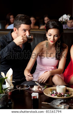 glamourous young couple eating ice-cream, drinking coffee - stock photo