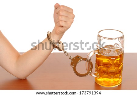 Glas of beer with handcuffs as symbol for alcohol abuse - stock photo