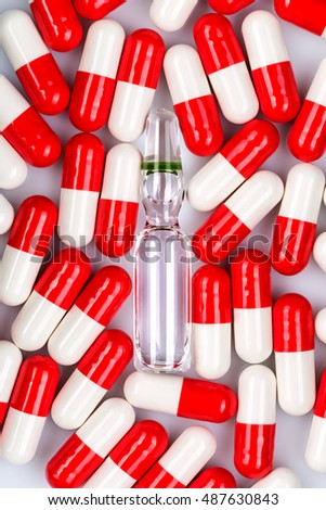 glass ampoule with liquid inside surrounded by many red-white capsules