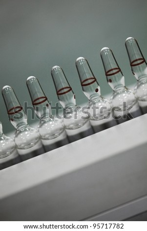 glass ampoules filled with liquid medicament close up - stock photo