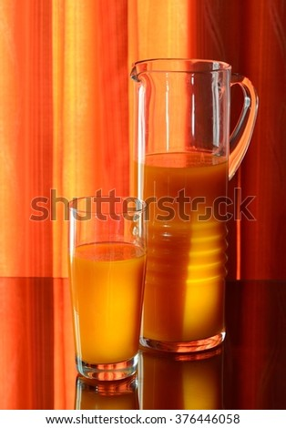 Glass and a carafe of pumpkin  juice. The sun's rays on the glass surface