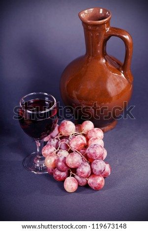 glass and a jug of red wine on a dark background - stock photo