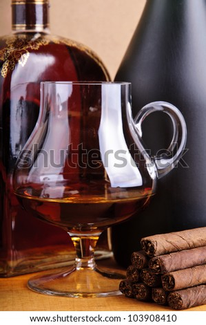 glass and bottle of brandy with cigarillos