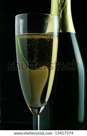 Glass and bottle of champagne close-up over black background - stock photo