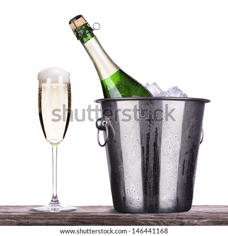 glass and bottle of champagne in Metal ice bucket  on a wooden vintage table isolated on a white background