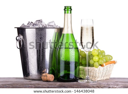glass and bottle of champagne in Metal ice bucket with grapes and butterfly on a wooden vintage table isolated on a white background