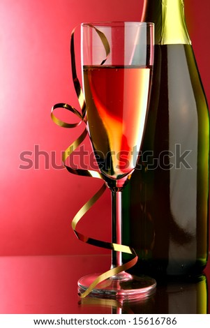 Glass and bottle of champagne with gold streamer ove red background - stock photo