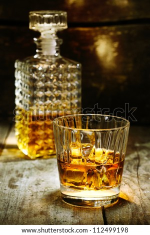 Glass and bottle of hard liquor like scotch, bourbon, whiskey or brandy on wooden background with copyspace - stock photo