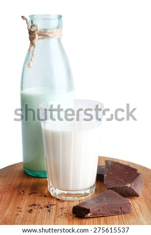 Glass and bottle of milk with chocolate chunks on wooden cutting board isolated on white