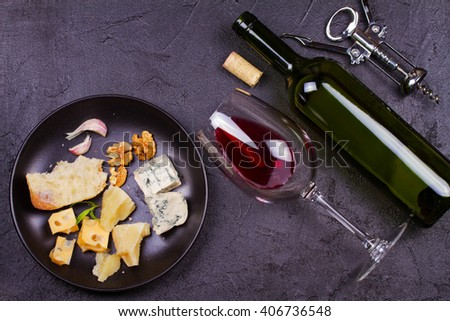 Glass and bottle of red wine, cheese, bread, garlic, nuts on gray stone texture background. View from above, top studio shot - stock photo
