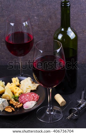 Glass and bottle of red wine, cheese, bread, garlic, nuts, salami on gray stone texture background - stock photo