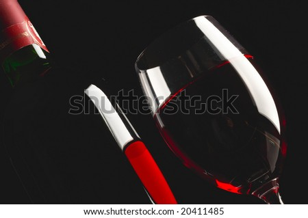 Glass and bottle of red wine on black - stock photo