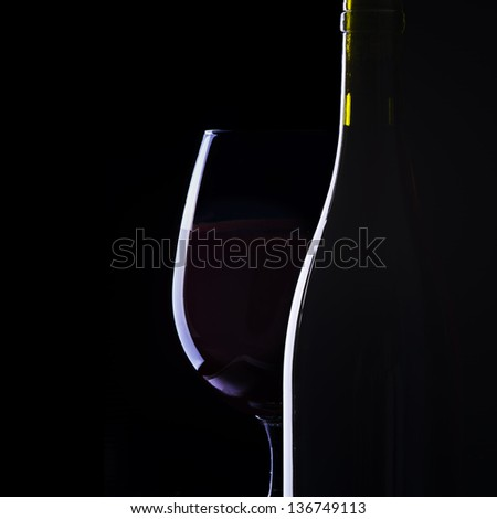 Glass and bottle of red wine on black background
