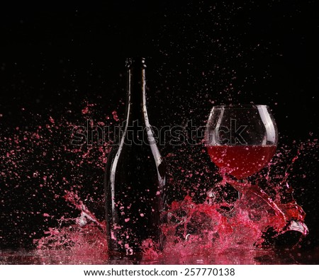 Glass and bottle of red wine splash on black - stock photo