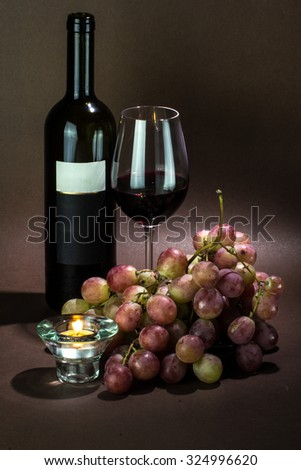 glass and bottle of red wine with bunch of pink grapes with burning candle