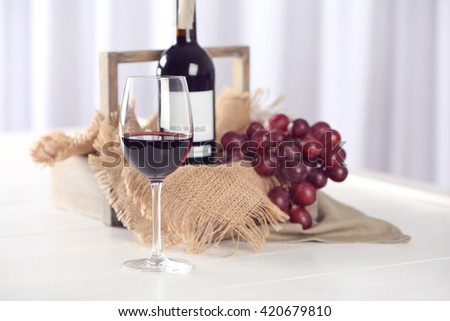 Glass and bottle of red wine with grape on blurred background - stock photo