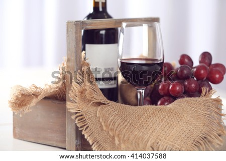 Glass and bottle of red wine with grape on table closeup - stock photo