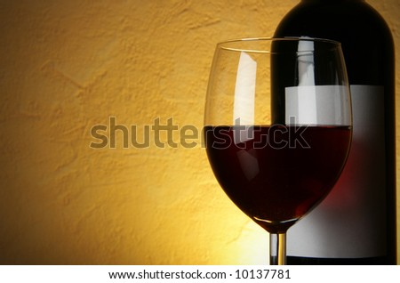 Glass and bottle of red wine with space for your text on left - stock photo