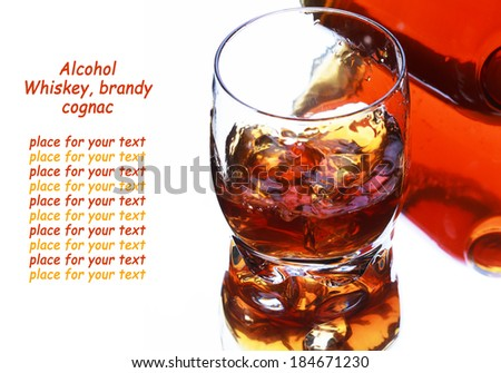 Glass and bottle of whiskey with splash on light background, selective focus on the glass - stock photo