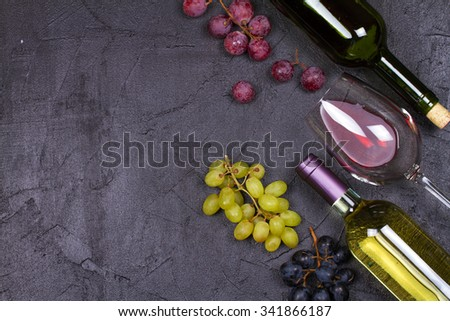 Glass and bottle of wine and grape on gray stone texture background. View from above, top studio shot