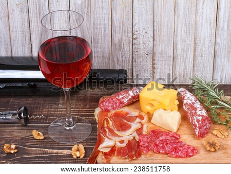 Glass and bottle of wine, cheese and prosciutto on wooden background. Still life - stock photo
