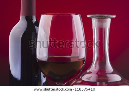 Glass and bottle of wine over red background