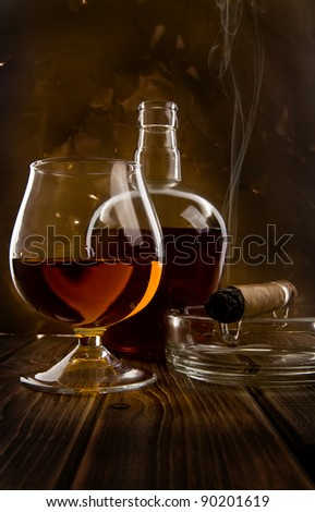 glass and bottle with a cigar on a wooden table - stock photo