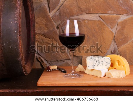 Glass and bottles of wine, cheese and prosciutto, old wooden barrel