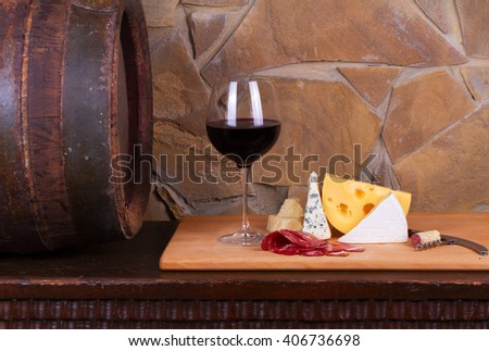 Glass and bottles of wine, cheese and prosciutto, old wooden barrel - stock photo
