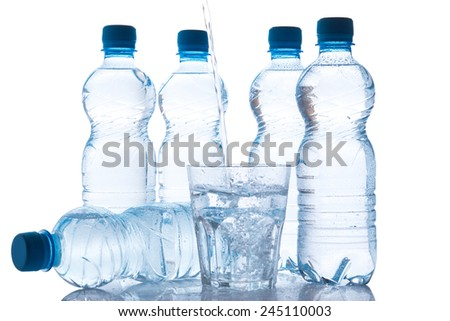 Glass and bottles with fresh water on white background