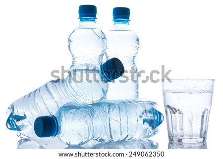 Glass and bottles with fresh water on white background - stock photo