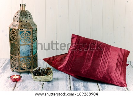 Glass and bronze coloured metal lantern with candle, basket of dates and red silk cushion - stock photo