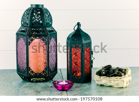 Glass and bronze coloured metal lanterns with candle and basket of dates - stock photo