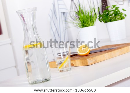 glass and carafe with refreshing lemonade on a kitchen counter - stock photo