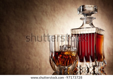 glass and decanter of brandy on a old stone background - stock photo