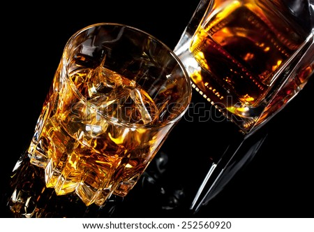 Glass and decanter of whiskey shot at an angle on black glass - stock photo