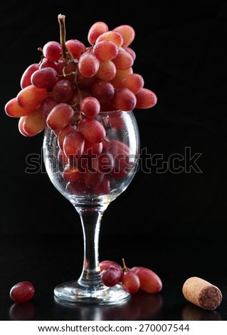 glass and grapes on the table and a dark background - stock photo