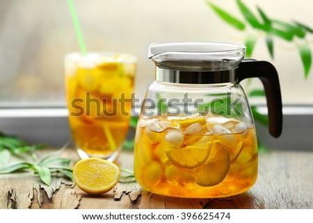 Glass and jar of iced tea with lemon on a windowsill - stock photo