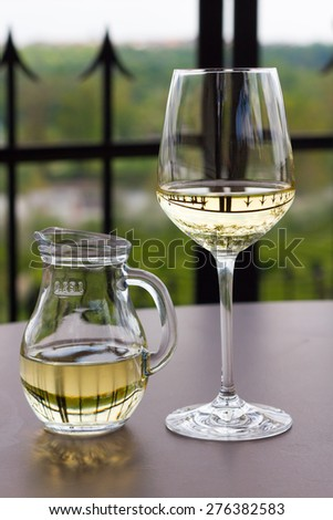 Glass and jug with white wine