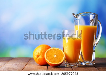 Glass and pitcher of orange juice on wooden table on natural background - stock photo