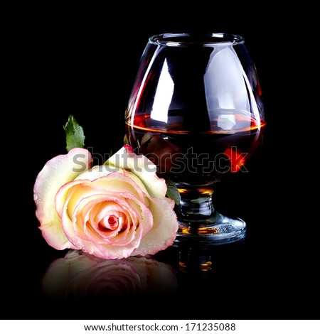 Glass and rose. Alcohol and flower. Glass with drink and a pink rose. - stock photo
