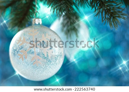 Glass ball with snowflake hanging on tree.
