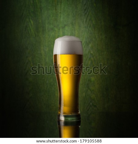 glass beer on wooden background with st.patrick logo - stock photo